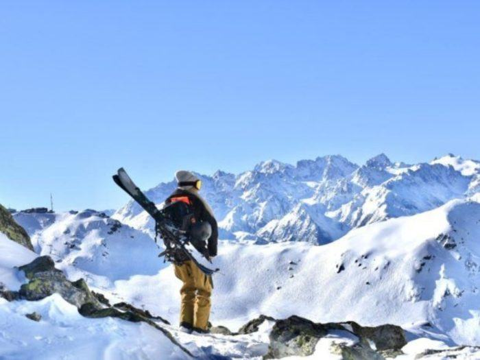 Standing with skis on a mountain