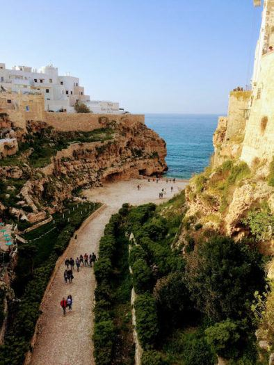walk to the beach with towering cliffs in polignano a mare puglia italy