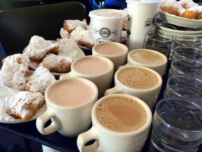 tray of beignets and cafe au lait in cafe du monde new orleans