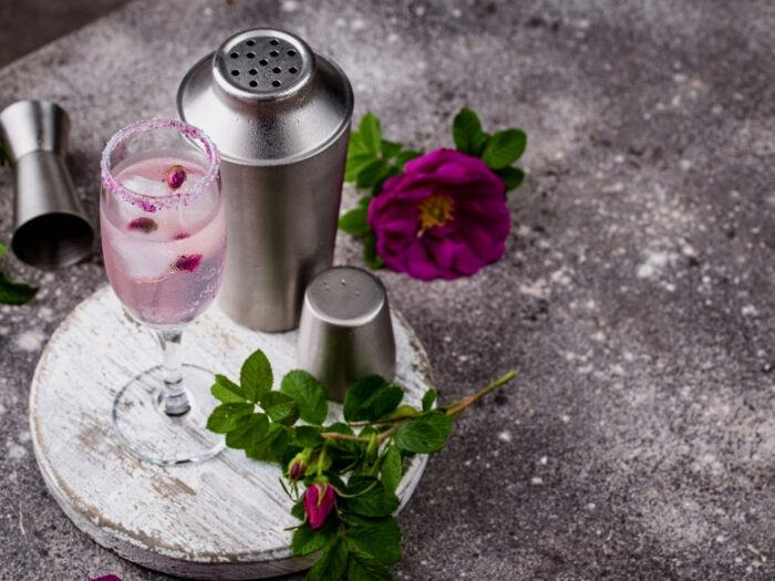 Rose coloured cocktail on wooden board