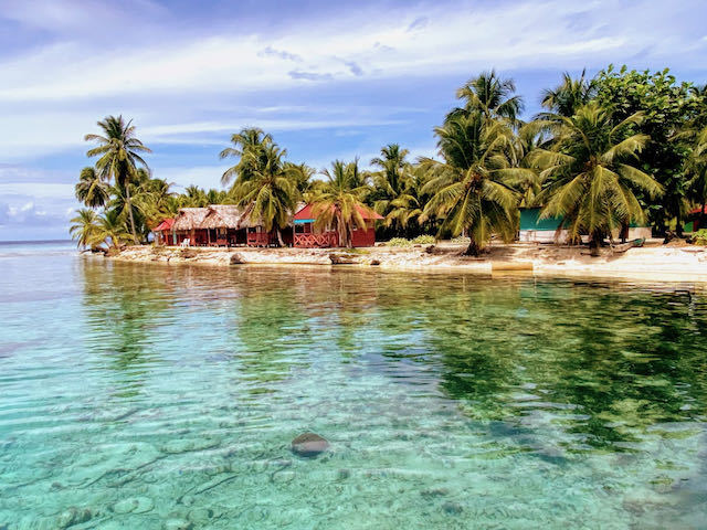 island with palm trees and huts san blas islands in panama